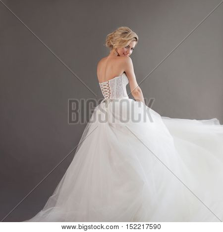 Charming young bride in luxurious wedding dress. Pretty girl in white. Emotions of happiness, laughter and smile, gray background, place for your text on the right