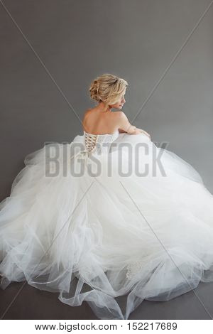 Charming young bride in luxurious wedding dress. Pretty girl in white. Gray background.