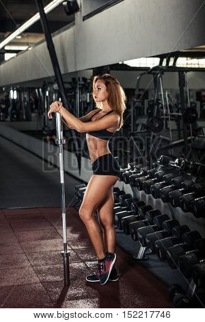 Attractive young athlete with muscular body. Woman in sportswear posing in gym