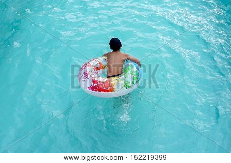 Active boy plays in outdoor swimming pool jumping inside inflatable ring