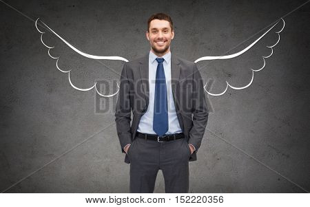 business, angel investor, safety, security and people concept - smiling young businessman with wings drawing over gray concrete background