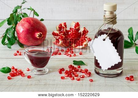 Glass bottle of pomegranate balsamic cream near ripe pomegranate, pomegranate slices, seeds, gravy boat on a light white wooden background. Pomegranate balsamic cream and pomegranates. Horizontal.