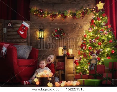 Merry Christmas and Happy Holiday! Two cute little children girls decorate the Christmas tree.