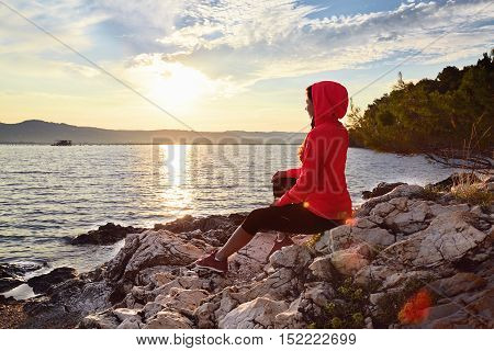 Runner resting from routine exercise. Happy jogger relaxing at the beach after run sitting on the stones and looking at the sea. Active young woman enjoying sunrise.