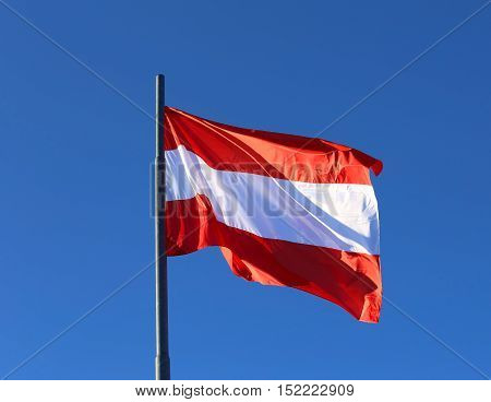Austrian Flag Waving In The Blue Cloudless Sky