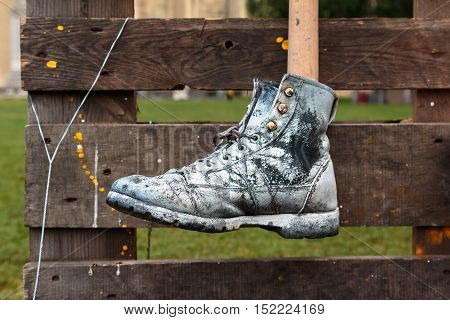 Hanged Black Shoe Painted in White Color Wooden Slat in Background