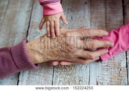 Close up. Unrecognizable grandmother and her granddaughters holding hands. Studio shot on white wooden background.