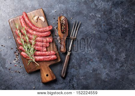Raw sausages and ingredients for cooking. Top view with copy space on stone table