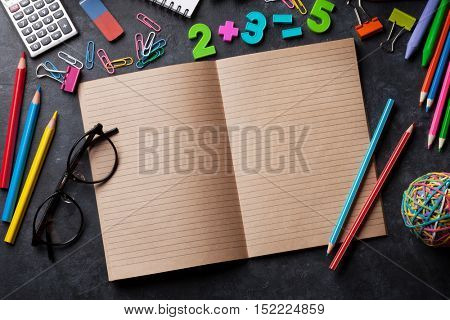 Supplies over chalk board for your text. Back to school concept with copy space