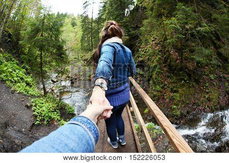 People walking across wooden bridge through mountain river. Follow me concept