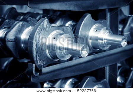 Close - up of crankshaft of parts in automobile production line.