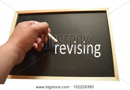 hand holding chalk with the word revising background on a blackboard with chalk