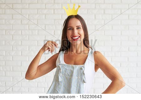 Happy smiling woman wear white singlet and holding decorate crown, white brick wall on background