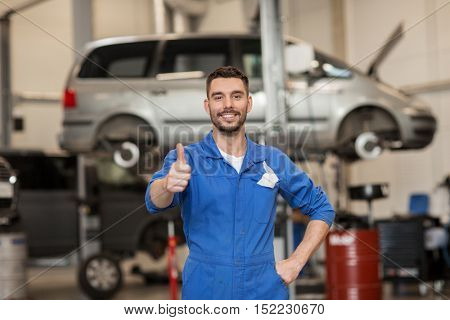 car service, repair, maintenance, gesture and people concept - happy smiling auto mechanic man or smith showing thumbs up at workshop