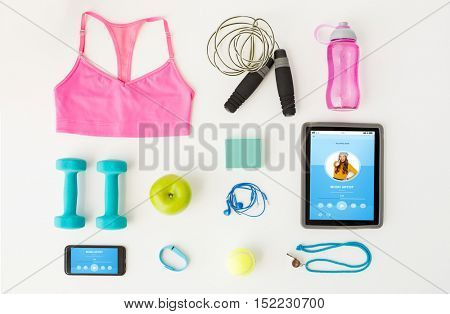 sport, fitness, healthy lifestyle, technology and objects concept - close up of tablet pc computer with smartphone and sports stuff over white background