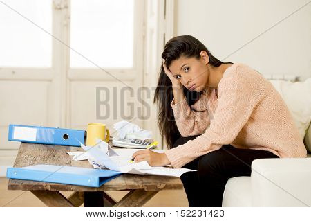 young sad latin woman at home living room couch calculating monthly expenses worried in stress with bank papers and documents in paying taxes mortage debt and cost of living concept