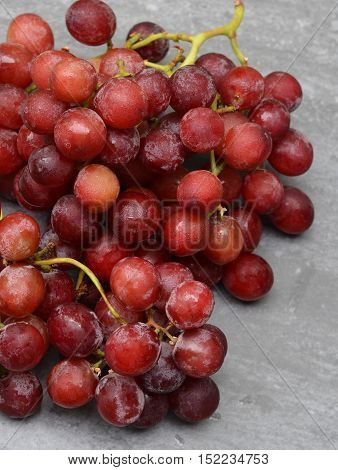 Bunch of Red Seedless Grapes: Shown on a grey background. Close up. Above view.