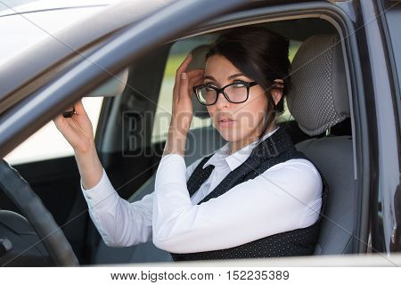 happy smiling young business woman in the car looking at the mirrow