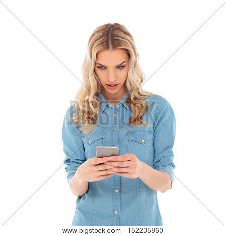 surprised casual blonde woman texting on her smartphone on white background