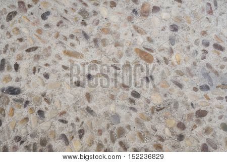 Small stones of shapes and colors together in cement