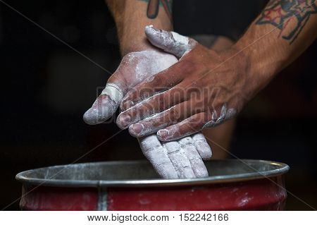 Closeup of male hands with talc powder. Sportsman preparing for cross fit, gymnastics or lifting training.