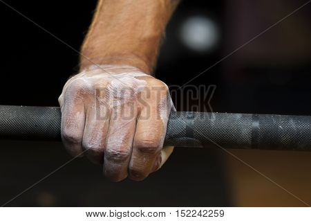 Male hand with powder holding barbell. Weightlifting powerlifting or cross fit training.
