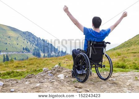 Young man in a wheelchair enjoying fresh air in a sunny day on the mountain.