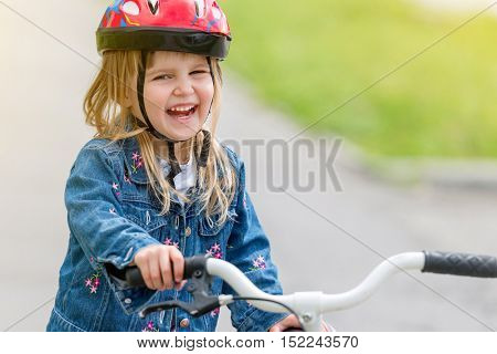 cute little girl in helmet and denim jacket riding bicycle