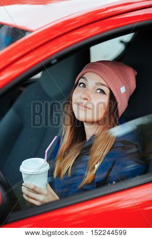 Stylish Sporty Brunette Woman In Trendy Urban Outwear Driving A Car With Big White Disposable Cup St