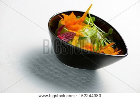 Salad in a small black bowl.