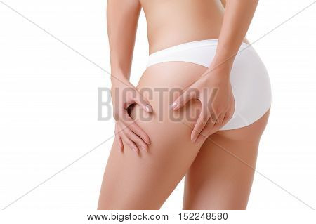 Female body care and beauty concept - close up of woman in underwear touching buttock over white background. Checking cellulite, woman hip, close up of beautiful female body legs, perfect woman figure