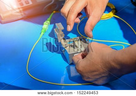 Technician using cleaver cutting optic fiber on blue table with meter.