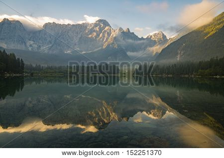 Julian Alps reflected in the lake Laghi di Fusine a beautiful morning, artistic photography