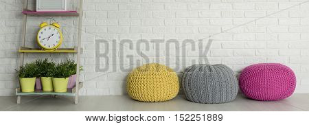 Colorful Poufs And A Shelf With Plants