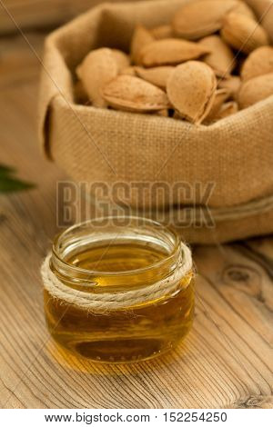 Almond oil and almonds on an old wooden background, selective focus