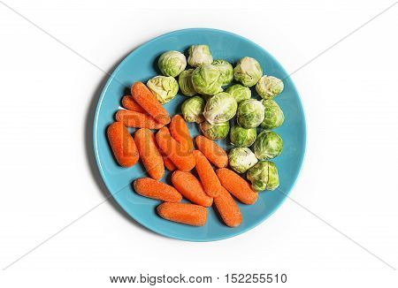 Vegetarian and vegan food isolated on white. Baby carrots and baby brussels sprouts on a plate