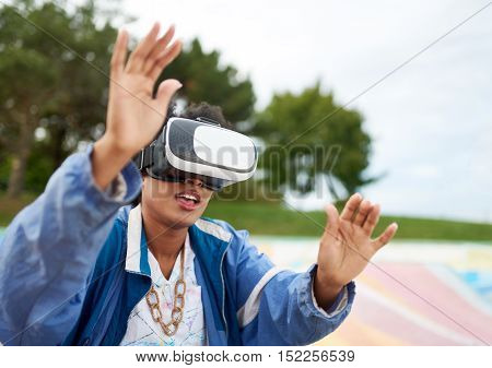 Smiley young African American woman alienated by new technology wearing VR goggles in a skate park outside