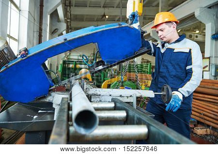 industrial male worker operating bandsaw in manufacturing factory