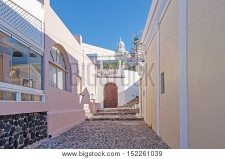 Thira Greece - November 10 2015: One of the typical narrow streets on the greek island Santorini in the southern Aegean Sea with its cobblestoned road white buildings and art galleries