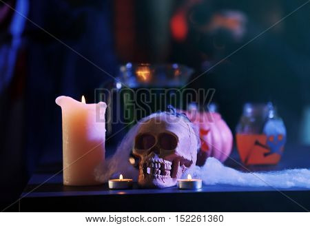 Human skull, spiderweb and candle on blurred background, close up. Halloween concept