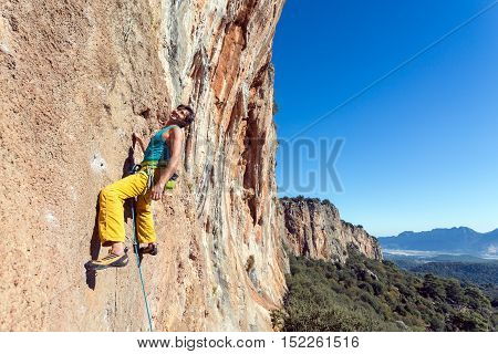 Mature male extreme Climber smiling face enjoying dangerous ascent on red orange vertical high natural rocky Wall blue clear Sky sunshine weather