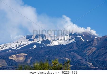Mount Etna an active stratovolcano from the south with the smoking peak in the upper left snowy flanks and cable car line in the Province of Catania Sicily Italy.