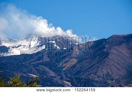Mount Etna an active stratovolcano from the south with the smoking peak snowy flanks a lateral crater in the centre and a cable car line in the Province of Catania Sicily Italy.