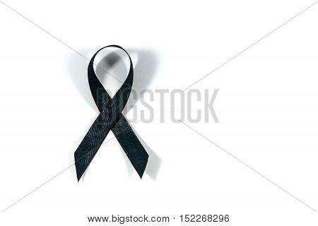 Black awareness ribbon isolated on white background. Mourning and melanoma symbol