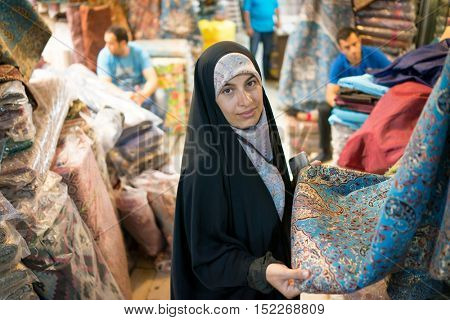 Beautiful Muslim woman spending time on traditional Iranian bazaar market street between people for shopping