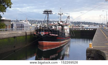 SEATTLE, WASHINGTON STATE, USA - OCTOBER 10, 2014: Hiram M. Chittenden Locks with large commercial fishing vessel docked in a ship canal