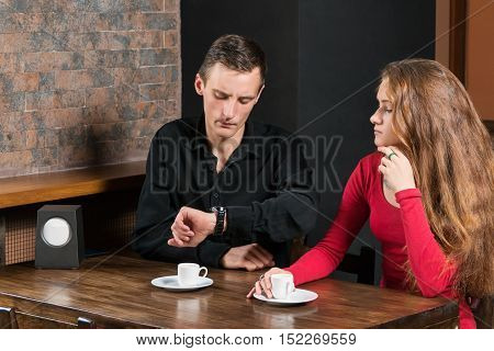 On a date at a cafe for a wooden table and a cup of coffee man exasperated looks at the watch on the hand
