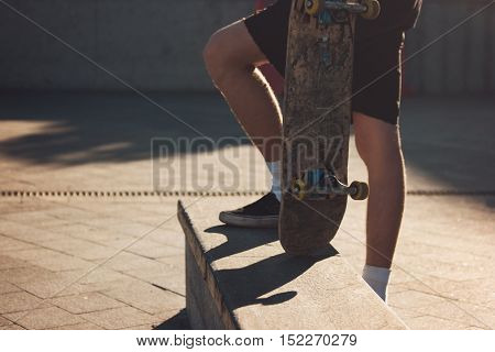 Feet of a skateboarder. Person with skateboard outdoors. Mastery starts from the simple. Ride with me.