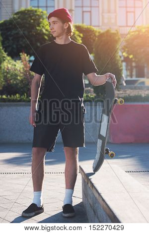 Guy holding skateboard. Skater outdoors at daytime. Live by your own rules. Young and stubborn.