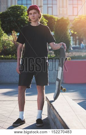Young man holding skateboard. Skater standing outdoors. My sport is my passion. Against the grain.
